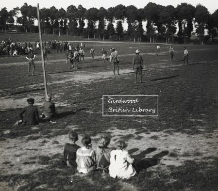 Enfants, soldats indiens et britanniques jouant au football